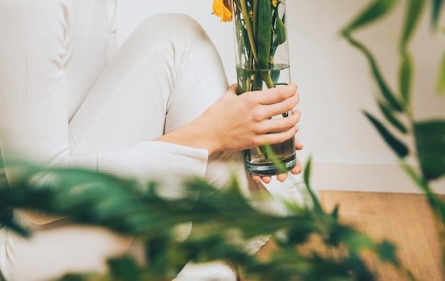 Vrouwenzitting op vloer met bloemen in vaas