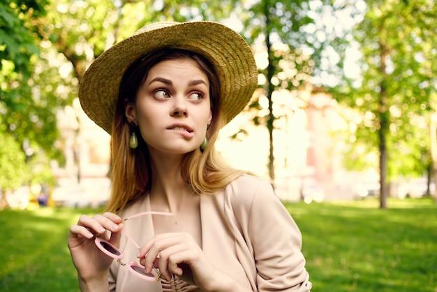 Vrouwenzonnebril en een hoed in het park groene gras