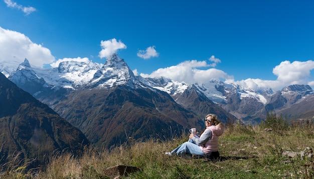 Vrouwreiziger drinkt koffie met uitzicht op het berglandschap