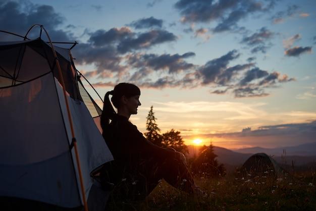 Vrouwtje zit in tent boven op de berg genieten van de zonsondergang op wazig heuvels