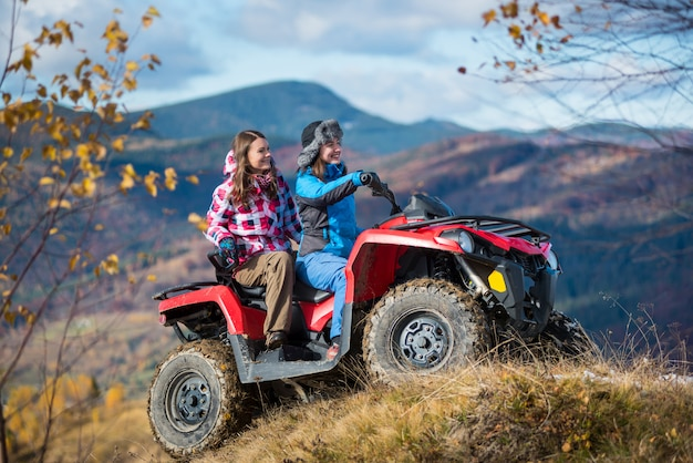 Vrouwtjes atv-bestuurder op besneeuwde heuvels