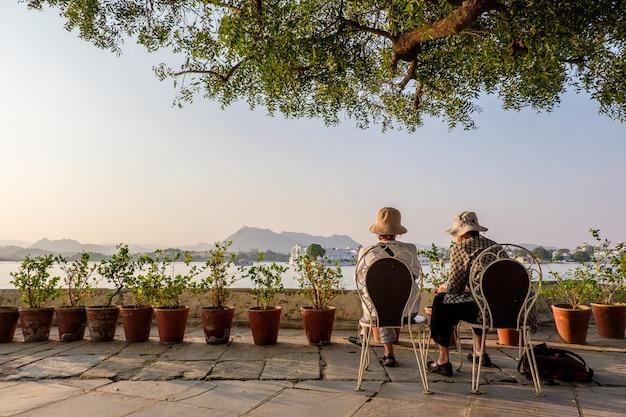 Vrouwtjes die hoeden dragen die op stoelen dichtbij bloempotten zitten die de bergen in de verte bekijken