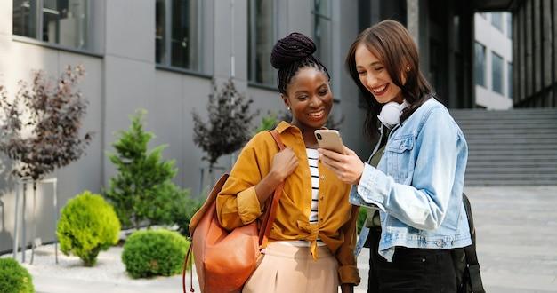 Vrouwtjes van gemengde rassen praten en kijken naar iets op de mobiele telefoon op straat in de stad. mooie multi-etnische jonge vrouwen chatten en het gebruik van smartphone. vrolijke vrienden roddelen. roddels.