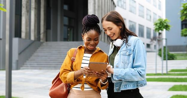 Vrouwtjes van gemengde rassen praten en kijken naar iets op tablet op straat in de stad. mooie multi-etnische jonge vrouwen chatten en gadgetcomputer gebruiken. vrolijke vrienden roddelen. roddels.