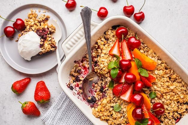 Vruchten en bessen haverafbrokkeling in ovenschotel op grijze achtergrond, hoogste mening.