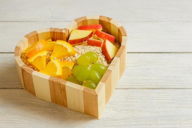 Vruchten hart op de houten achtergrond. gezond voedselconcept.