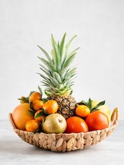Vruchten in geïsoleerde mand. verse ananas, mandarijnen, grapefruit, lieverd, peren en kaki fruit. witte achtergrond.