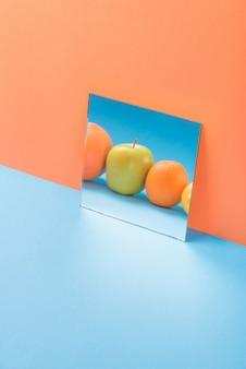 Vruchten in spiegel op blauwe tafel geïsoleerd op oranje