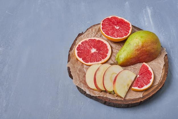 Vruchten op een houten bord op blauw
