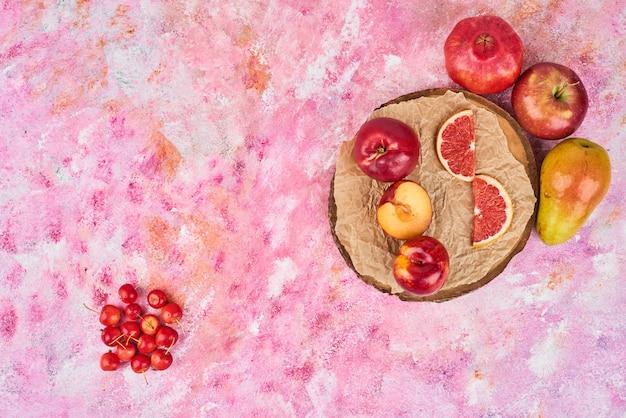 Vruchten op een houten bord op roze, bovenaanzicht.