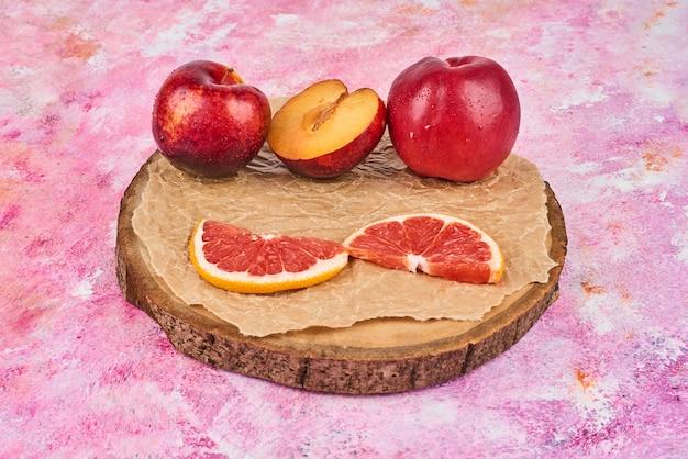 Vruchten op een houten bord op roze.