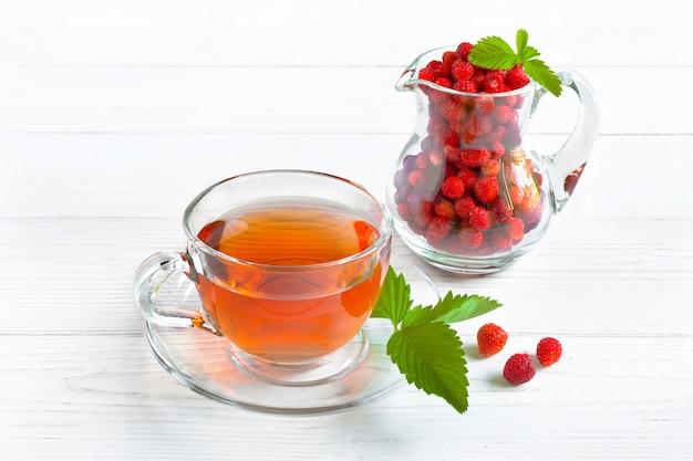 Vruchten rode thee met aardbeien in glazen beker op houten tafel, op lichte ondergrond