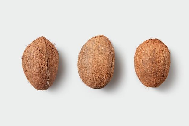 Vruchten van rijpe verse hele kokosnoten op een witte achtergrond met kopie ruimte. vegetarisch voedselconcept.