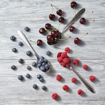 Vruchtenpatroon van verse zomerbessen op grijze achtergrond. concept van gezond detoxdieet, antioxidant biologisch fruit. bovenaanzicht.
