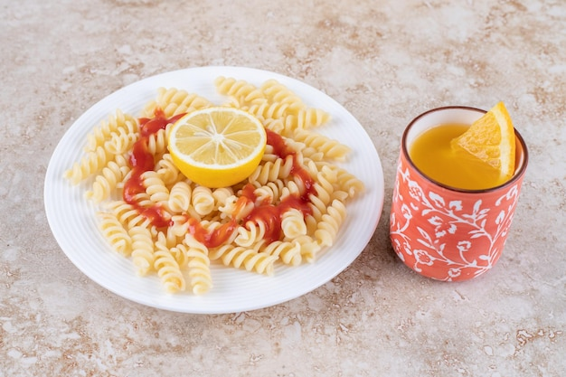 Vruchtensap en macaroni schotel met schijfjes citroen op marmeren oppervlak.