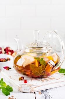 Vruchtenthee met bessen, citroen, limoen en muntblaadjes in glazen theepot op wit licht houten oppervlak