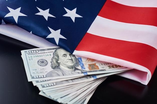 Vs nationale vlag en dollarbiljetten op een donkere achtergrond. zakelijke en financiële concept