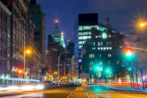 Vs, new york city. nacht manhattan. kruispunt nabij cooper square, straatverlichting, verkeerslichten en sporen van autokoplampen