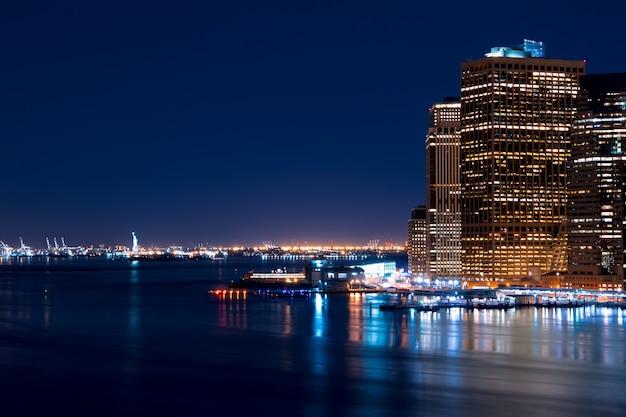 Vs. new york city. nacht. uitzicht op de wolkenkrabbers van manhattan, upper bay en het vrijheidsbeeld in de verte