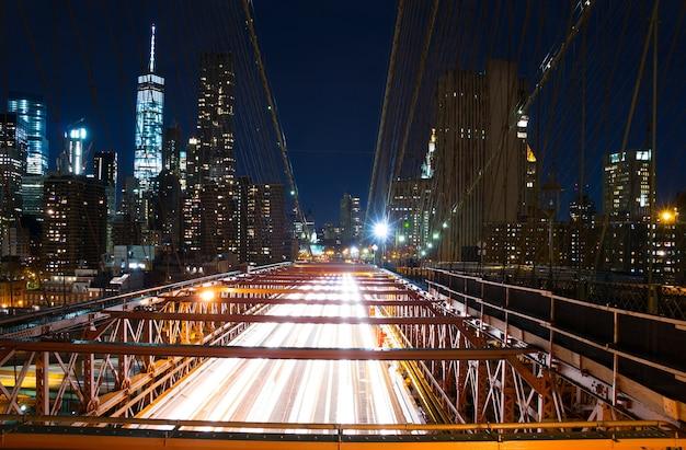Vs. new yorkse stad. nacht. verkeer op de brooklyn bridge en uitzicht op de wolkenkrabbers van manhattan