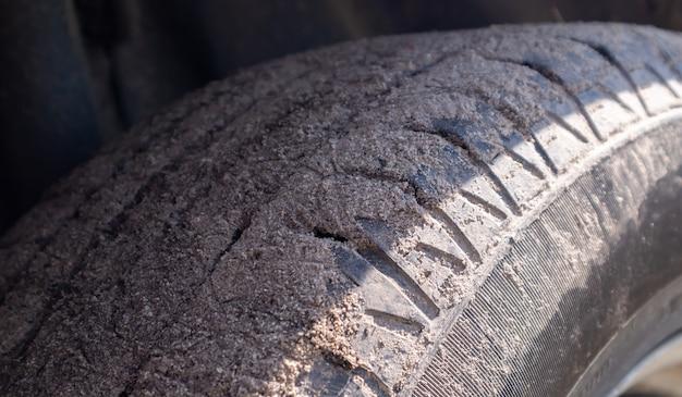 Vuil autowiel op een grondweg naar het platteland. close-up detail van een band. transport, rijden en auto concept. de auto kwam vast te zitten in het zand.