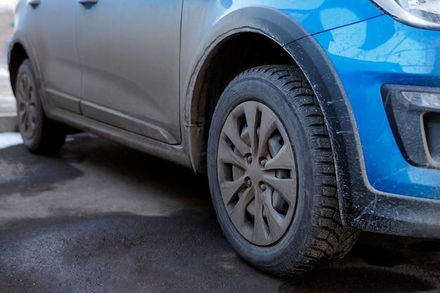 Vuil en stof op de carrosserie en wielen van een autochemie en zout