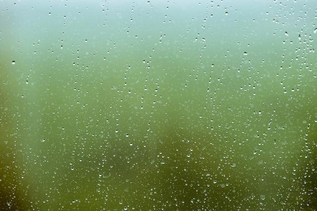 Vuil glas met druppels regen. regendruppels op groene heldere bokeh. groen buiten venster. druppeltjes en vlekken close-up. gedetailleerde transparante textuur in macro.