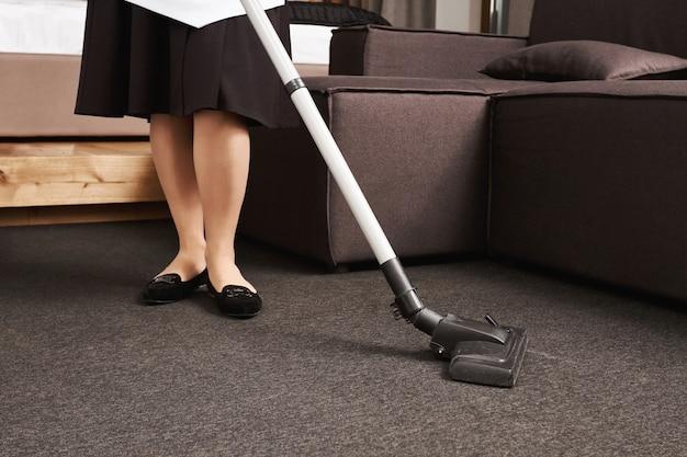 Vuil heeft geen kans om te overleven. bijgesneden portret van vrouw in meid uniforme schoonmaakvloer met stofzuiger, werkend in het huis van haar werkgever, veeg al het vuil en de rommel die ze achterlieten na het feest