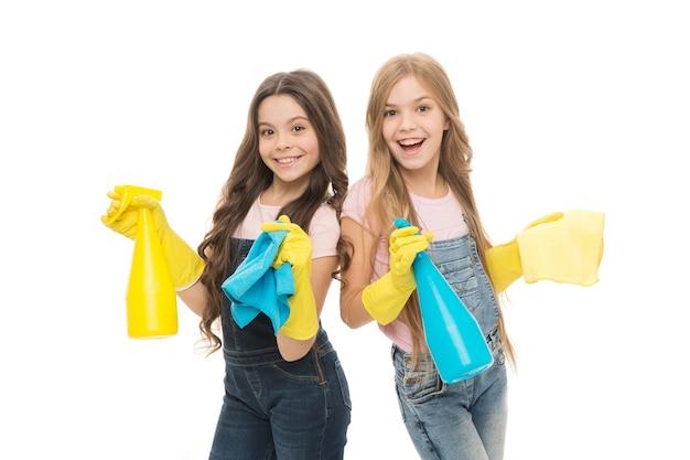 Vuil is niet welkom in ons huis. schattige kleine meisjes die rubberen huishoudhandschoenen dragen. kleine kinderen die huishoudelijke spuitflessen vasthouden. genieten van huishoudelijke activiteiten. huishoudelijke hulp bieden.