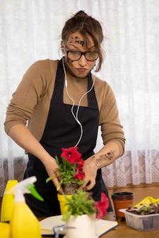Vuile aantrekkelijke vrouw zet emotioneel bloemen in potten in haar landhuis
