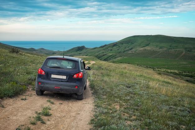 Vuile auto-crossover. velden met wijngaarden. prachtige natuur met heuvels. zwarte zee op de achtergrond.