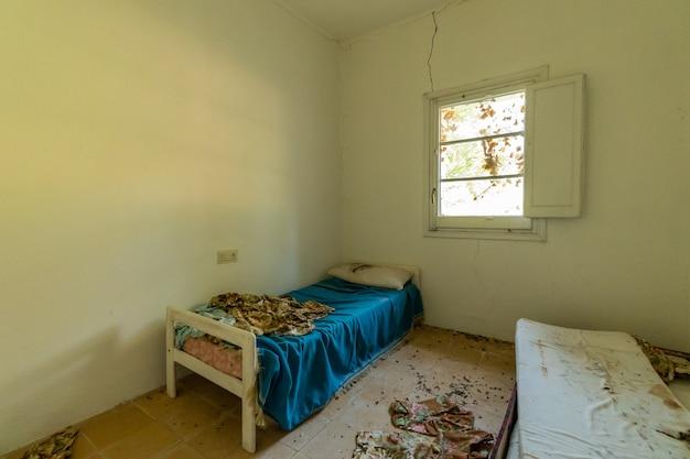Vuile bed in een kamer van een verlaten huis