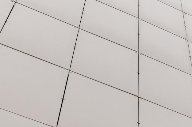 Vuile beige vierkante tegels op muuroppervlak, diagonale weergave.