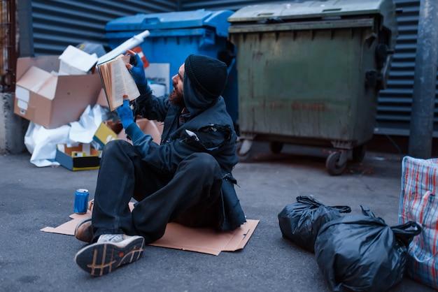 Vuile dronken bedelaar ligt in de vuilnisbak bij de vuilnisbak