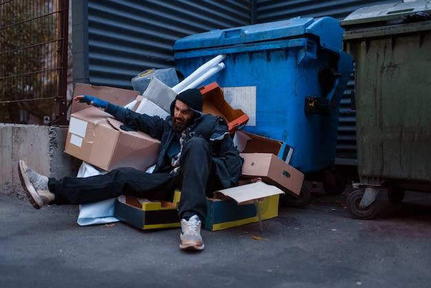 Vuile dronken bedelaar ligt in vuilnis bij de vuilnisbak op straat in de stad.