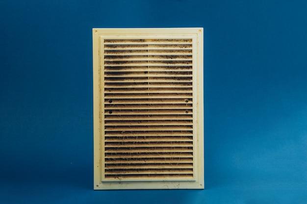Vuile en stoffige plastic ventilatie grill voor het huis op een blauwe achtergrond.