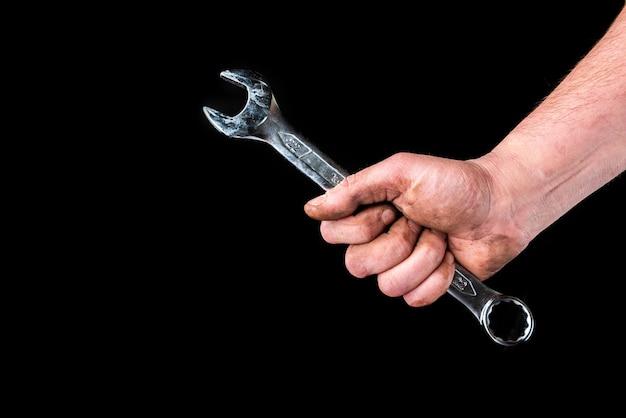 Vuile hand met moersleutel op zwart.