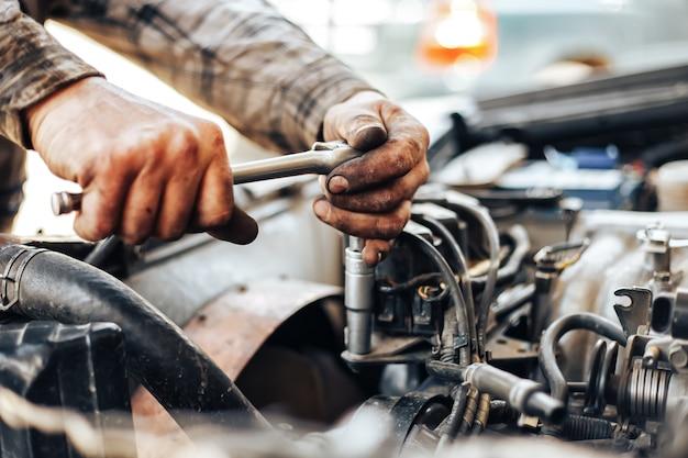 Vuile handen van automonteur reparing auto