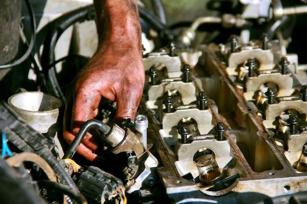 Vuile handwagons van een automonteur die de noten aandraait tijdens het repareren van een auto