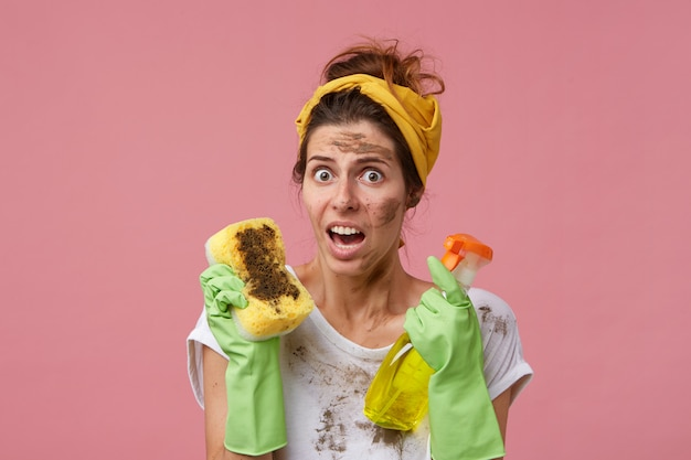Vuile huishoudster doet de voorjaarsschoonmaak met rubberen beschermende handschoenen en een hoofdband op het hoofd, kijkend met geïrriteerde en verbaasde blik die stof en schoonmaak haat. huishoudelijk werk en klusjes