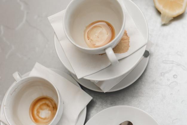 Vuile kopjes met vlekken van koffie en thee op een metalen tafel in de keuken op kantoor