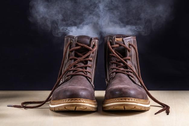 Vuile laarzen met een onaangename geur. zweterige schoenen na lange wandelingen en actieve levensstijl. schoeisel moet worden schoongemaakt en geurtjes worden verwijderd. schoenverzorging en glans