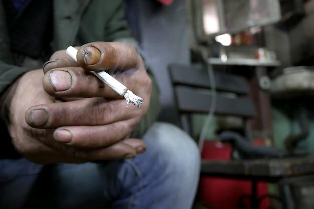 Vuile onverzorgde handen van een man met een sigaret