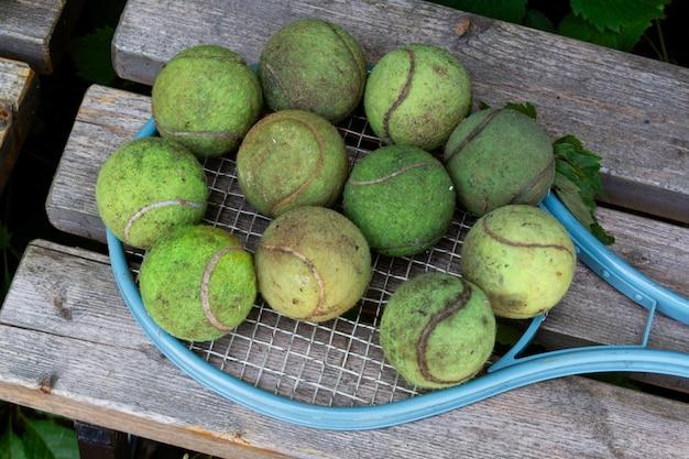 Vuile oude tennisballen en vintage tennisracket op houten bank vrijetijdsactiviteiten buitenspellen