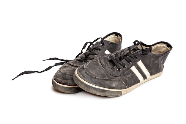 Vuile oude zwarte sneakers geïsoleerd op een witte achtergrond