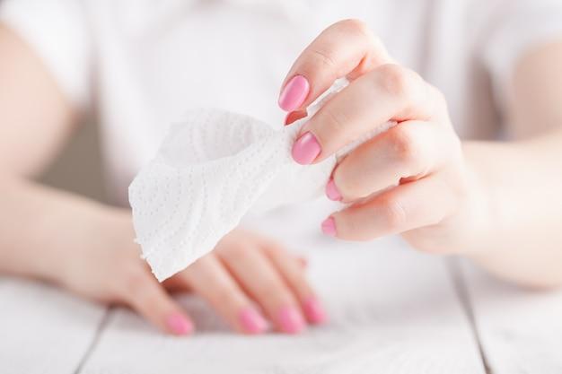 Vuile papieren zakdoekjes op vrouwelijke hand het een rommel maken van in een vuilnisbak