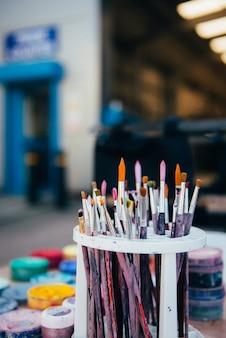 Vuile penselen in de plastic bak van het penseel