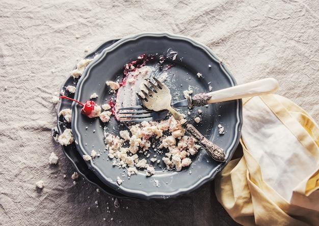 Vuile plaat en vork na het eten van een slagroomtaart met een kers. slagschaduw