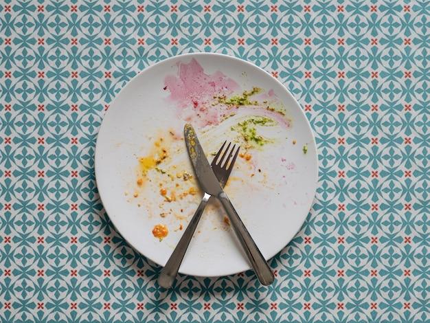 Vuile plaat na gezonde vegetarische paleo lunch witte plaat en kleurrijke vuile na eigeelbiet en groene pesto over blauw tafelkleed bovenaanzicht of plat leggen