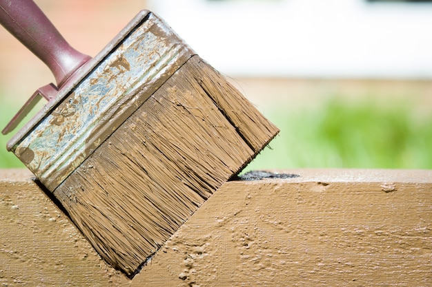 Vuile rode verfborstel die op stuk hout na het werk ligt; landschapsarchitectuur; tuin-